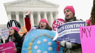 Feminist demonstrators hold signs outside the US Supreme Court building on 25 March, 2014.