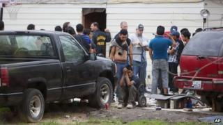 People wait outside a suspected stash house in southeast Houston on 19 March 2014
