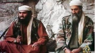 An image from a video showing Suleiman Abu Ghaith seated left of Osama Bin Laden, on 12 September 2001
