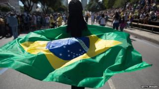 A woman walks holding a Brazilian flag behind her