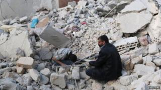 Civilians search under the rubble at a site hit by what activists said were barrel bombs dropped by forces loyal to President Bashar al-Assad in the Karam Homad district of Aleppo (26 March 2014)