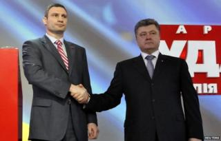 Ukrainian politicians Vitaly Klitschko (L) and Petro Poroshenko shake hands during a party meeting
