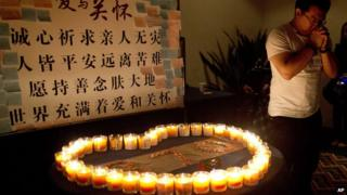 A man, a relative of a Chinese passenger on board Malaysia Airlines Flight 370, prays near candles before a briefing with Malaysian officials at a hotel in Beijing, China (March 31, 2014)