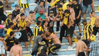 Fans of Uruguay's Penarol clash during the Uruguayan first division football derby against Nacional, at the Centenario stadium in Montevideo on November 24, 2013.