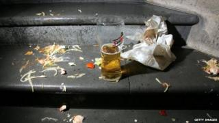 Discarded takeaway wrapper with a pint of lager, left on steps