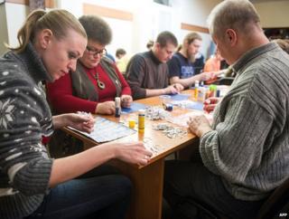 Volunteers in Kiev on 8 March 2014 piece together shredded documents found in the residence of former Ukrainian president Viktor Yanukovuch