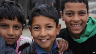 Children pose for a photo on the streets of Kashmir