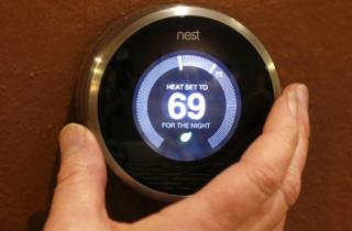 A hand is on the Nest smart heating thermostat