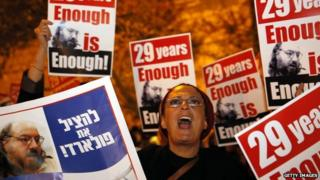 "An Israeli protesting the imprisonment of Jonathan Pollard holds up a sign reading ""enough is enough""."