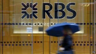 A woman carrying an umbrella walks past a branch of Royal Bank of Scotland