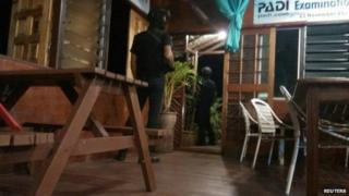 Armed men are seen near a door of Singamata Reef Resort hotel in Sabah on 2 April, 2014