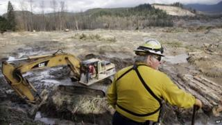 Benton County assistant fire chief Jack Coats surveys the landscape at the scene of a deadly mudslide as an excavator works below to clear a drainage channel, in Oso, Washington 2 April 2014
