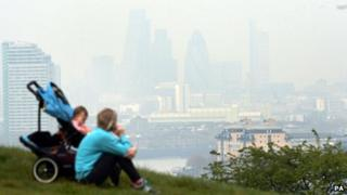A woman and child look over London's Canary Wharf, shrouded by smog, from Greenwich Park.