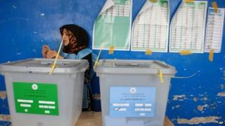 An Afghan employee of the Independent Elections Commission waits for voters standing beside ballot boxes at a polling station in Mazar-i-Sharif