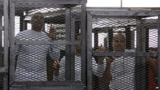 """Al-Jazeera English bureau chief Mohammed Fahmy, left, producer Baher Mohamed, center and correspondent Peter Greste, right, appear in a defendant""""s cage"""