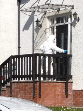 A forensics officer enters the house in Newtownabbey where a family was intimidated by an armed gang