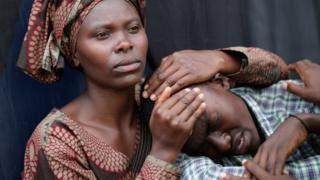 A woman consoles a 22-year-old man during the 20th anniversary commemoration of the 1994 genocide at Amahoro Stadium7 April 2014 in Kigali, Rwanda