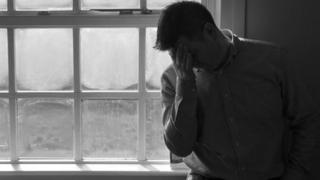 A man stands by a window with his head in his hands