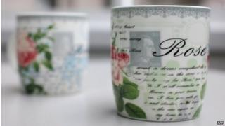 A coffee mug featuring a picture of a stamp with Adolf Hitler's portrait on it, postmarked with a swastika stamp