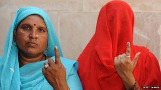 Two women showing their painted finger after voting in Indian general election