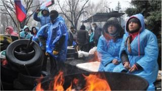 Pro-Russian activists warm themselves by a fire outside the Security Service building in the eastern Ukrainian city of Lugansk on 11/04/14