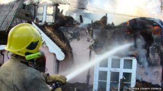 Firefighter at a thatched cottage fire in Barham