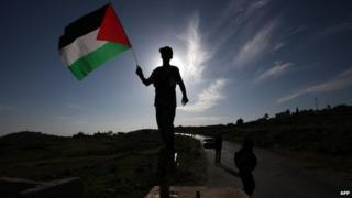 A Palestinian holds up a Palestinian flag near the village of Nabi Saleh (14 April 2014)