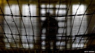 A prisoner at HMP Pentonville walks through an atrium May 19, 2003 in London