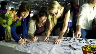 University of Calgary students and staff sign condolences on a University of Calgary banner during a memorial service for victims of the multiple fatal stabbing in northwest Calgary, Alberta 15 April 2014