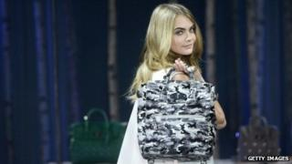 Model Cara Delevingne poses with a Mulberry handbag