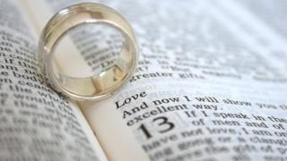 A wedding ring on an open page of the bible