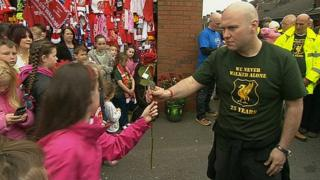 A walker hands a red rose to a child at the Anfield memorial