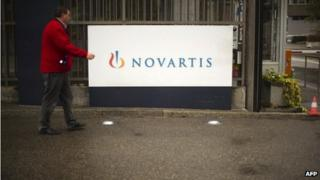 A man walking in front of a Novartis Logo