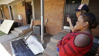 Residents look on as workers repair a front door, centre, at an apartment complex in Atlanta 10 April 2014