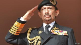 "Brunei's Sultan Hassanal Bolkiah salutes as the national anthem is played during celebrations for Brunei""s 30th National Day, in Bandar Seri Begawan on 23 February, 2014"