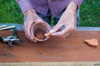 Man puts terracotta pieces into pot