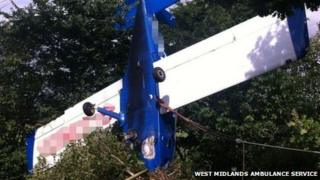 A blue plane resting nose down against a hedgerow