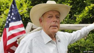 Nevada rancher Cliven Bundy stands in front of an American flag.