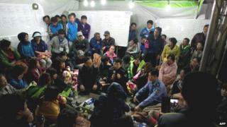 Coastguard police chief Kim Seouk Gyun (bottom centre), vice coastguard police chief Choi Sang Han (bottom right), and South Korean minister of Oceans and Fisheries Lee Ju Young (bottom left) attend a meeting with relatives of victims of the ferry disaster at Jindo harbour