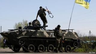 A Ukrainian soldier jumps off an armoured personnel carrier at a checkpoint in the village of Malinivka, east of Sloviansk in eastern Ukraine, 24 April 2014