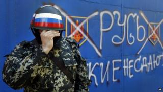 A pro-Russian militant adjusts his mask in Sloviansk