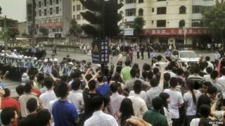 Workers protest during a strike as police stand guard at a crossroads near the factory area of Yue Yuen Industrial, in Dongguan, Guangdong province (18 April 2014)
