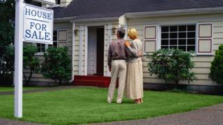 """A couple stands in front of a home with a """"for sale"""" sign in its yard."""
