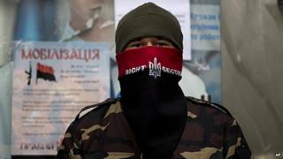 A masked man protects the entrance of a building transformed into a barracks in Kiev's Independence Square