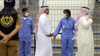 Workers wear mouth and nose masks during football match at King Fahad stadium. 23 April 2014