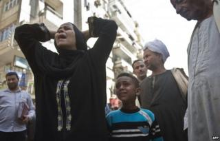 """Egyptians react outside the courtroom in Egypt""""s southern province of Minya after an Egyptian court sentenced Muslim Brotherhood leader Mohamed Badie and other alleged Islamists to death on April 28, 2014."""
