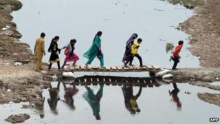 Pakistani residents cross the Ravi river in Lahore