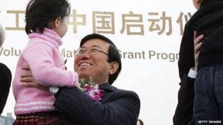 Li Chuncheng, secretary of the CPC Chengdu City Committee holds a child during the opening ceremony for the Intel Chengdu Assembly and Testing Plant, at Chengdu West Industrial Development Zone on 6 December, 2005 in Chengdu of Sichuan Province, China