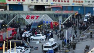 Security personnel gather near the scene of an explosion outside the Urumqi South Railway Station in Urumqi in northwest China's Xinjiang Uighur Autonomous Region on 30 April 2014