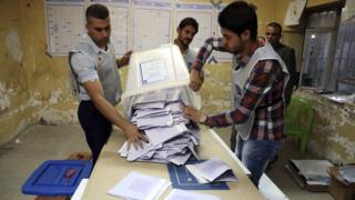 Electoral workers count ballots as polls close at a polling centre in Baghdad on 30 April 2014